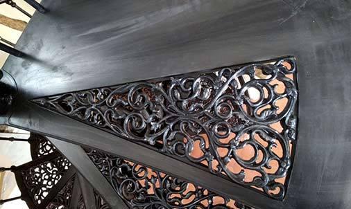 Détail d'une marche palière de l'escalier colimacon en fonte
