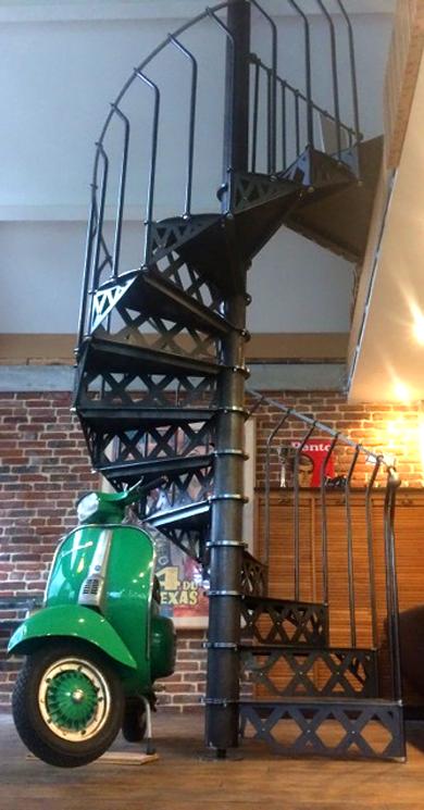 Scooter vert devant un escalier style Eiffel